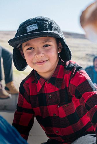 在水牛格子衬衫和帽子捕手可爱的孩子