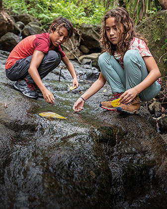 Two kids playing on a river rock trail