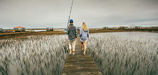 A man and woman walk on a dock in Performance Fishing Gear.