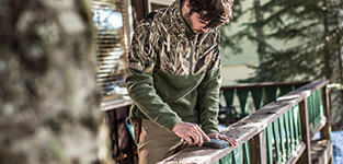 A man on a cabin porch in camouflage Columbia Performance Hunting Gear.