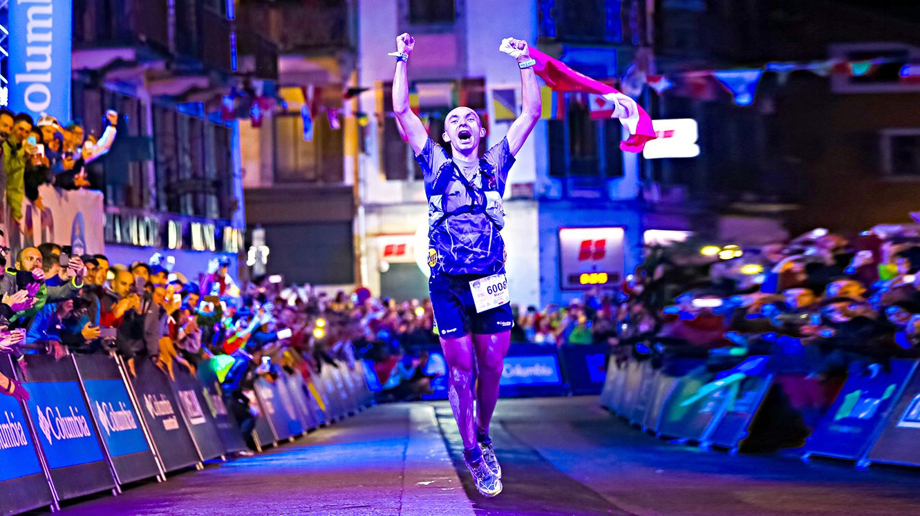A man celebrates at the UTMB finishing line amid cheering crowds in Chamonix.
