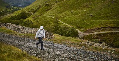 A person wearing an OutDry Extreme Eco jacket walking up a stony path.