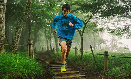 A man trail running with shoes featuring FluidGuide technology.