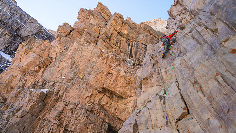 A climber is halfway up a mixed rock and ice route.