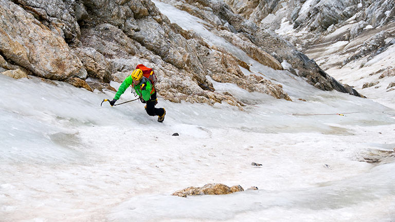 Image of an ice climber, head down, in the middle of a route.