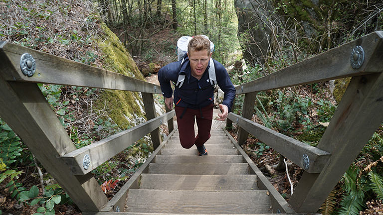 Mountain Hardwear Tim Emmett trains outside on a flight of stairs with backpack on.