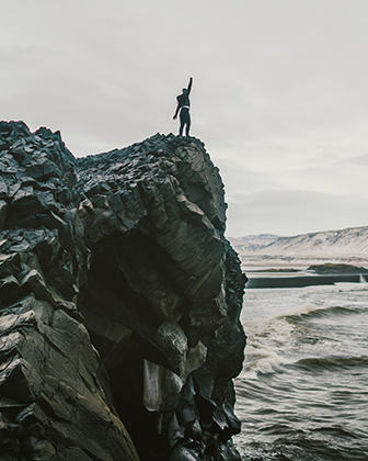 Someone standing triumphantly on a cold ocean cliff.