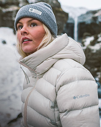 Woman in a white puffy jacket and beanie.