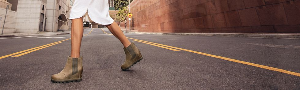 A woman walking in the city wearing Joan Wedge Chelsea boots