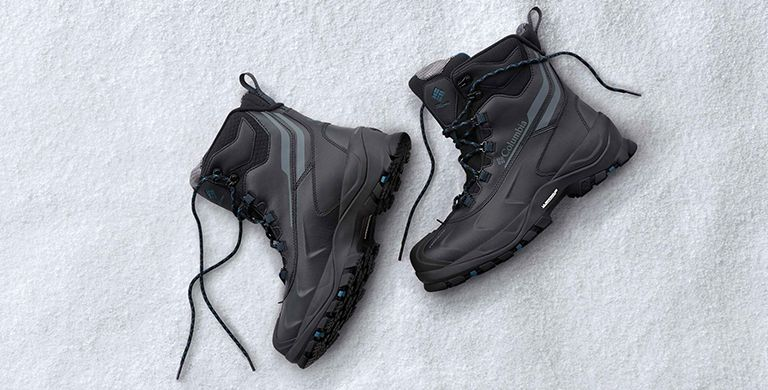 A pair of black boots lying on the snow.