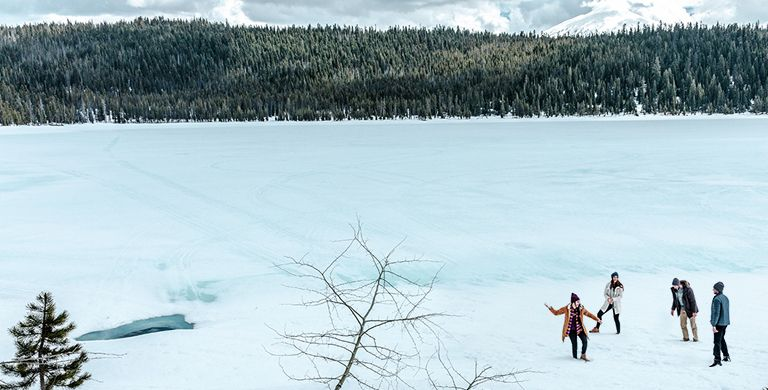 Four friends having a snowball fight next to a frozen lake.