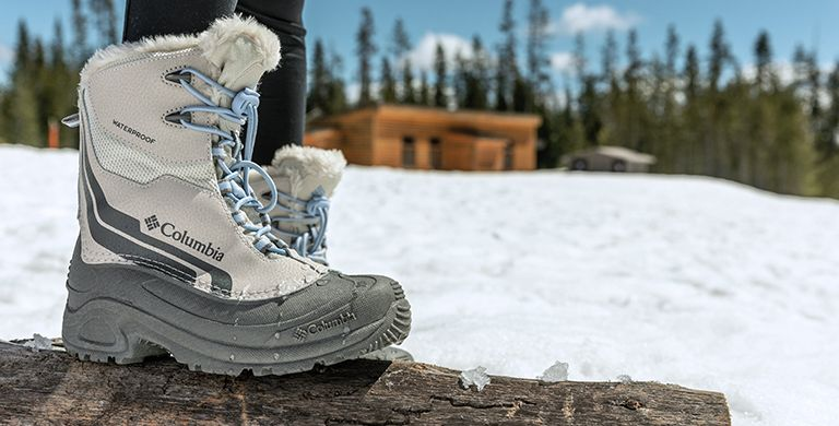 A close-up of gray, faux-fur-lined boots in the snow.