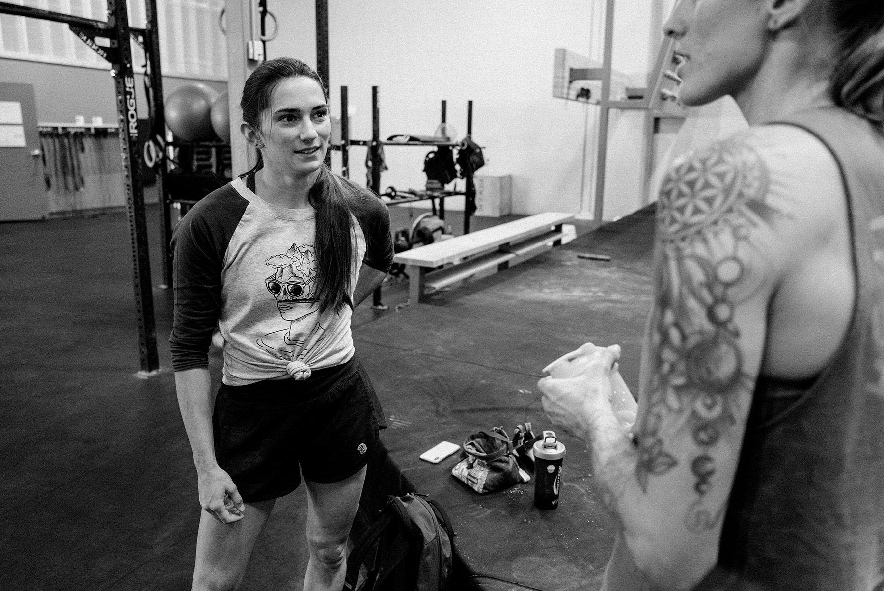 Black and white image of Kyra and Alex talking in between climbs at the gym
