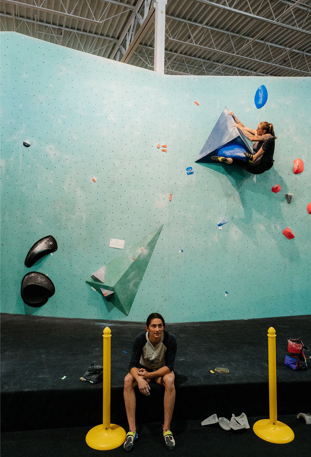 Kyra sits on the ground taking a break while Alex is near the top of a bouldering route behind her.