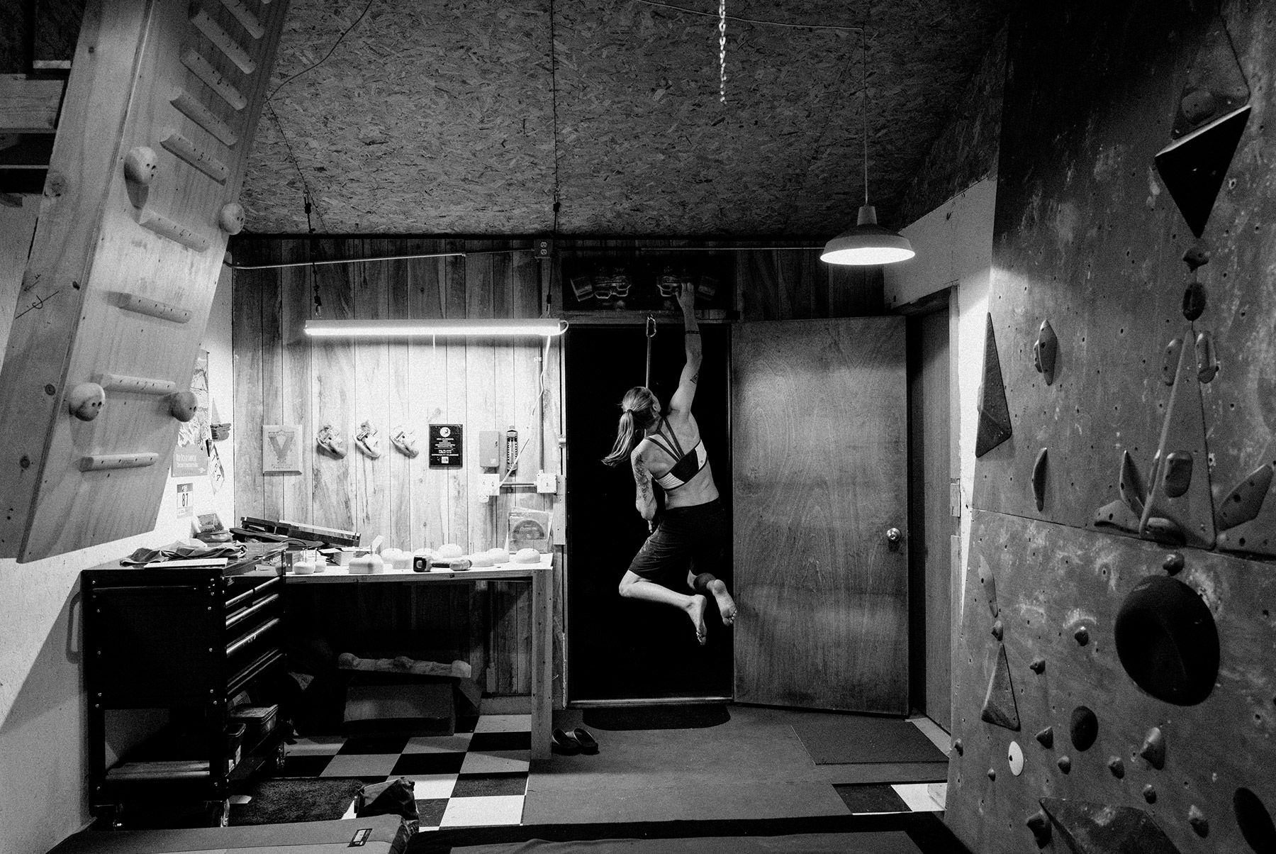 Black and white image of Alex doing hangboard exercises in her home gym