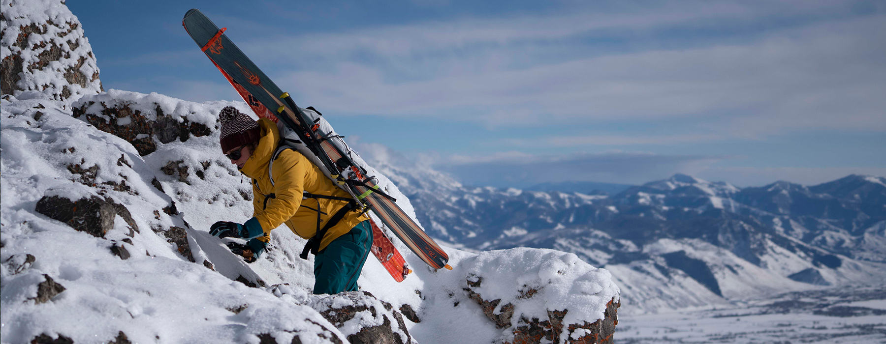 A backcountry skiier climbing some rock to get to the ultimate launching point