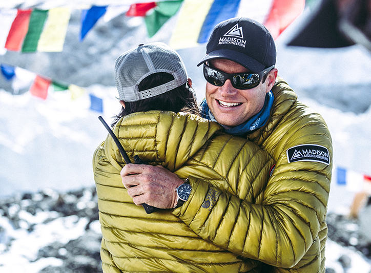Garrett Madison embraces one of the sherpa at Everest Base Camp wearing the Ghost Whisperer down jacket.