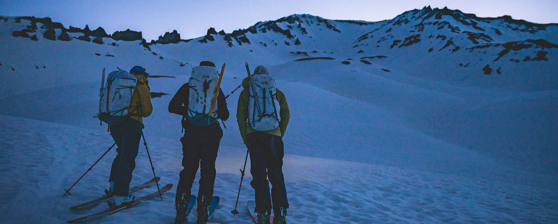 Three skiers planning their approach at dusk, looking at the mountain ahead