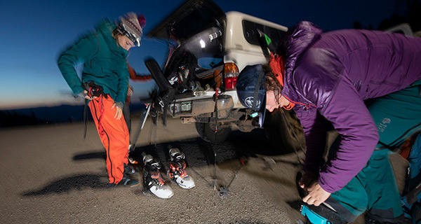 Blurry mid motion image of three skiers getting ready at the back of their truck, putting on ski boots and bibs at dusk.
