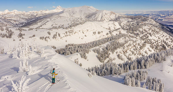 Two skiers overlook the beautiful snow-covered backcountry before skiing down a line.