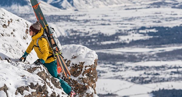Skier climbing up some rocks in the backcountry, with skis secured on Mountain Hardwear backpack.
