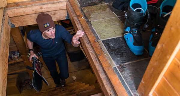 Mountain Hardwear Athlete Luke Smithwick walks upstairs in a ski hut, with old skis in hand.